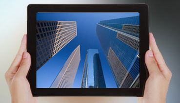 Hands holding ipad with commercial real estate photo on iPad